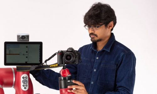 Headshot of Guru Subramani working on a robot