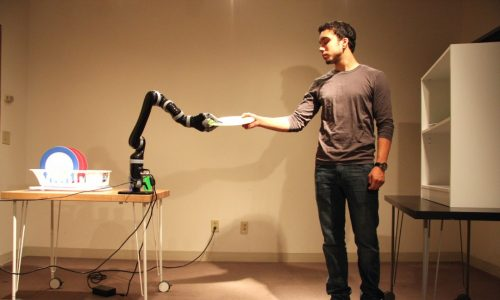 A researcher is handing a plate off to a single robotic arm attached to a desk